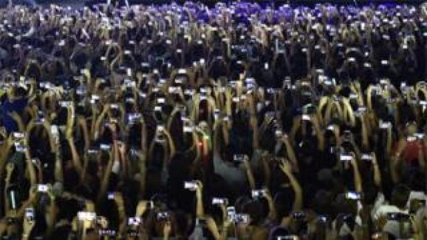 Fans use their phones at concert