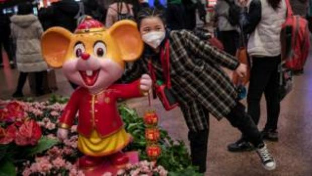 """A young Chinese girl wears a protective mask as she stands next to a display celebrating the upcoming """"Year of the Rat"""""""