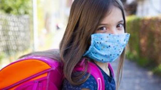 Schoolgirl wearing face covering