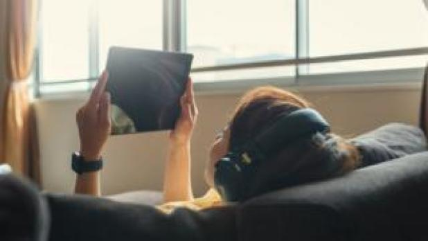 A woman watching a tablet device