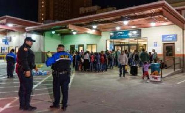 Police drop off asylum seekers at a bus station in Texas after their release from Ice detention