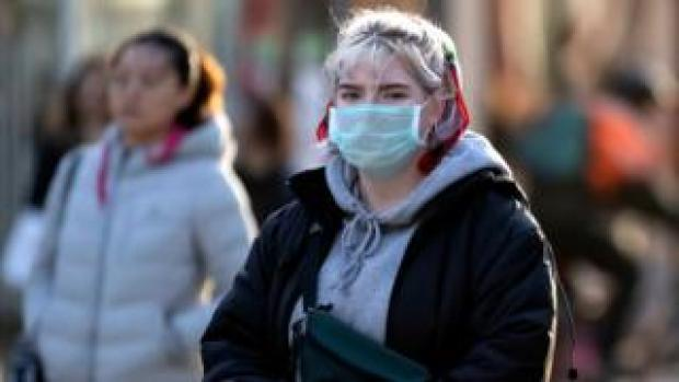 A woman wearing a facemask in Cardiff city centre during coronavirus outbreak, 2020