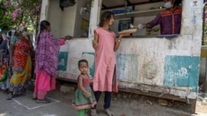 Homeless people receive free food offered by the Telangana state government during a 21-day government-imposed nationwide lockdown as a preventive measure against the COVID-19 coronavirus in Hyderabad