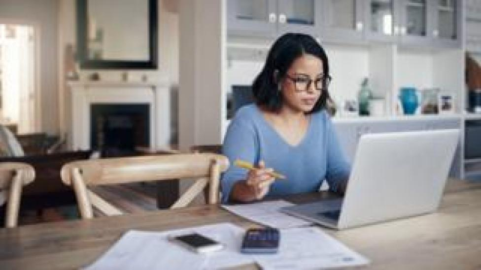 A woman sits at a desk working from home