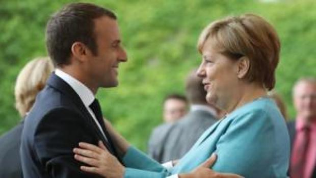 Emmanuel Macron, left, in his dark suit, hugs Angela Merkel, right, in a light blue jacket, at the June 2017 G7 Summit