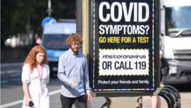 Woman and man walk past covid sign