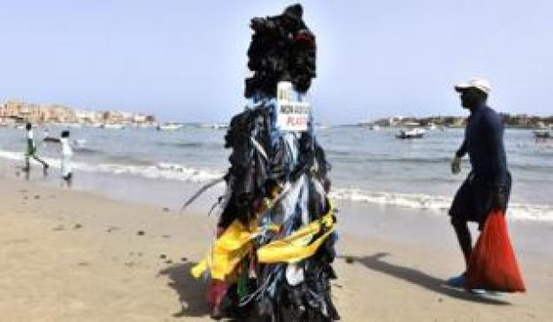 "A man wearing many plastic bags and wearing a placard reading ""Senegal clean. No to plastic bags"" walks along the beach of Ngor, one of the most frequented in the agglomeration of Dakar"
