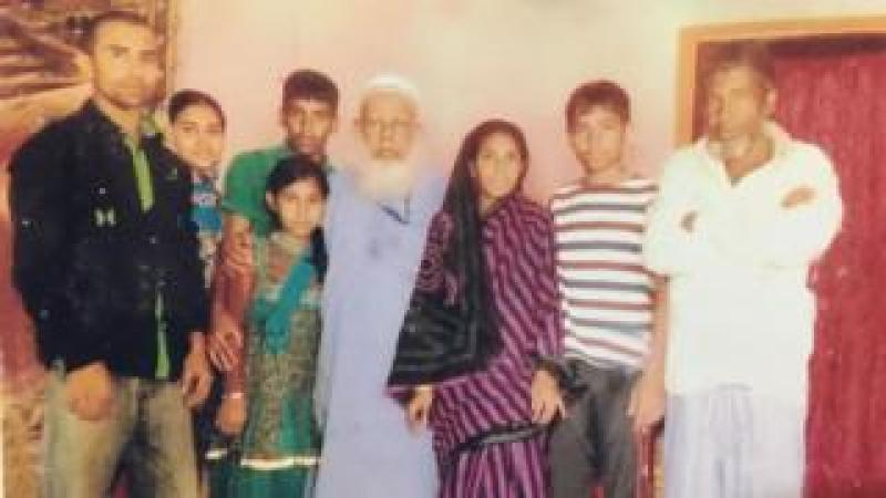 Kamru (centre) with family in Bangladesh