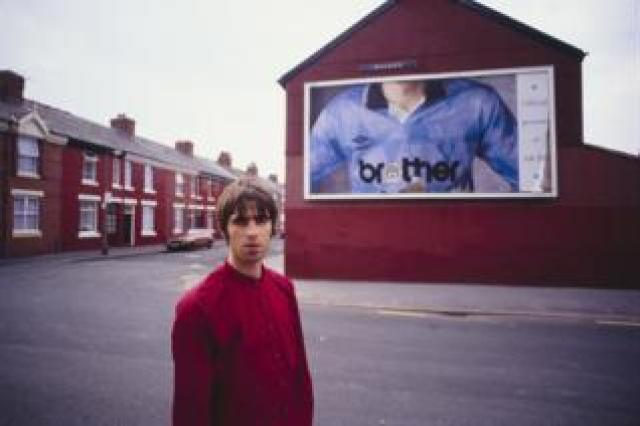 Liam Gallagher stood in front of a billboard featuring a Manchester City football shirt with a