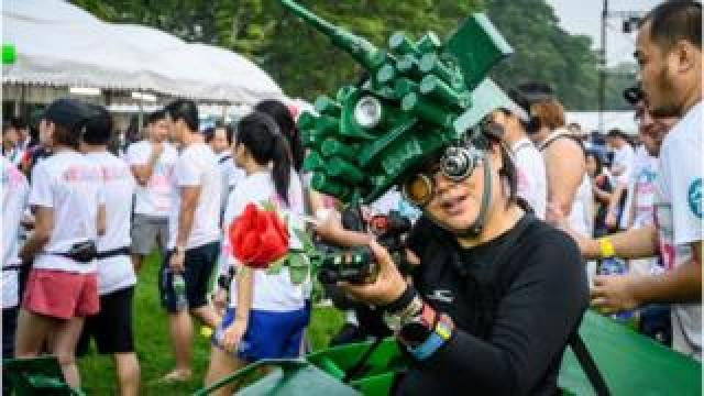 "A woman in a tank costume poses before a ""run against dictatorship"" in Bangkok"