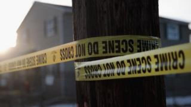 Police tape around a tree near a house in the US