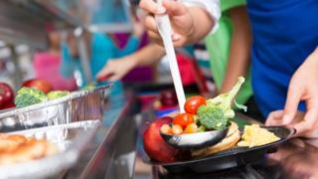 Close up of vegetables; students choosing food in school cafeteria - stock photo