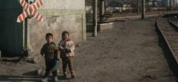 In a photo taken on November 21, 2017, children stand besides a railway track in the industrial city of Chongjin on North Korea's northeast coast.