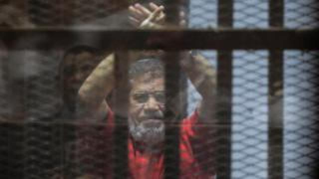 Former Egyptian President Mohamed Morsi raises his hands during a court appearance