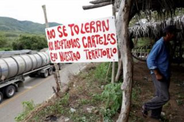 "A sign reads: ""We do not tolerate nor accept drug cartels in our territory"" at a checkpoint in Mexico"