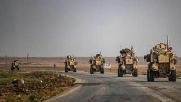 US military vehicles drive on a street in the town of Tal Tamr on October 20, 2019, after pulling out of their base
