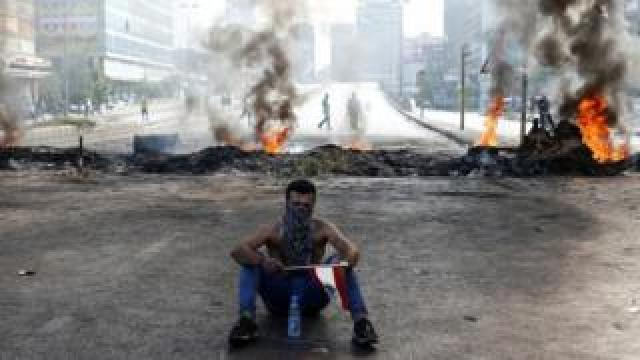 A protester sits in front of flames in Dora, Lebanon