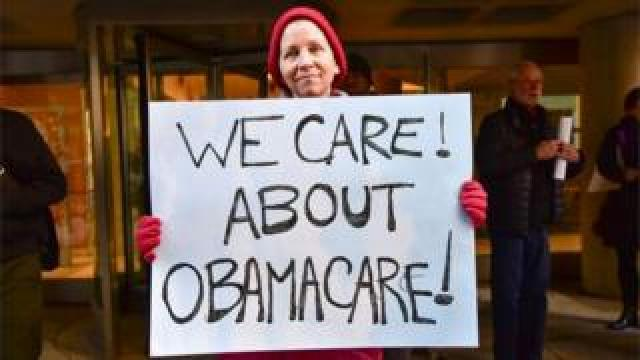 """Constituents speak-out and rally supporting the Affordable Care Act, organized by MoveOn.org outside Senator Pat Toomey""""s office on December 20, 2016 in Philadelphia, Pennsylvania."""