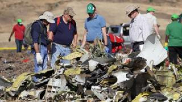 Investigators with the US National Transportation and Safety Board (NTSB) look over debris at the crash site of Ethiopian Airlines Flight ET 302.