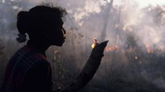 A girl in Arnhem Land, Australia, holds a small branch which flickers with flame