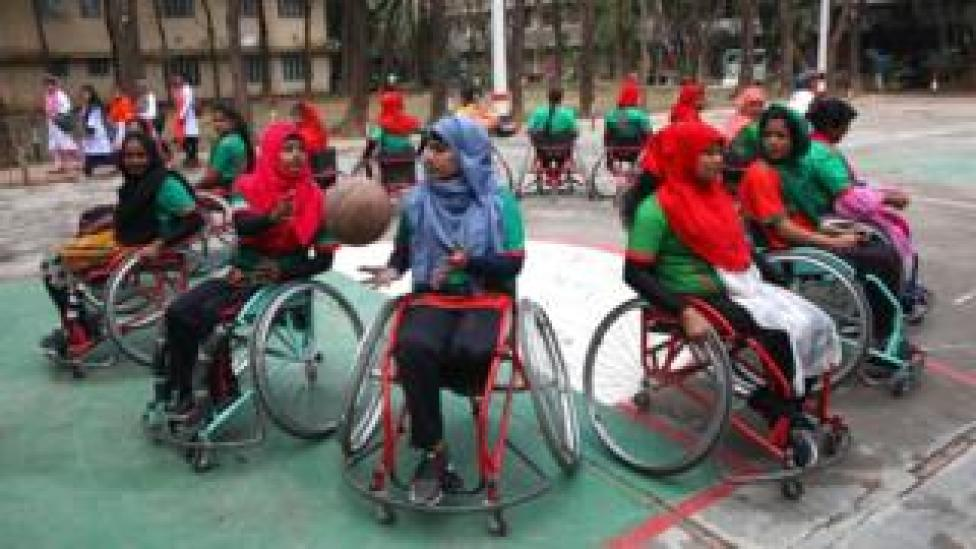 Bangladeshi women play basketball in a match organised by the Centre for the Rehabilitation of the Paralysed and the Red Cross to observe International Women's Day on the outskirts of the capital, Dhaka, 8 March 2020
