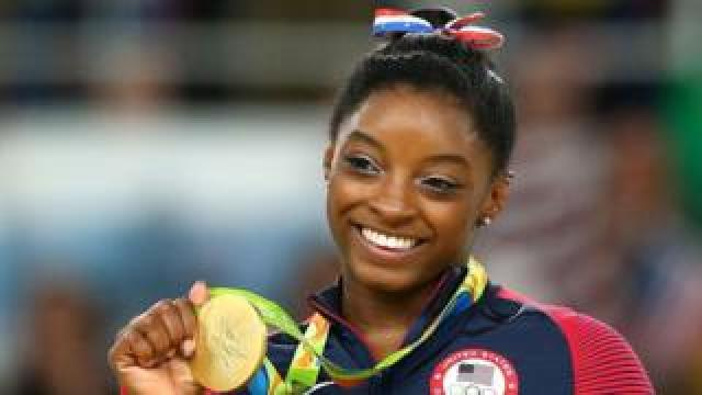 Simone Biles holds up one of the four gold medals she won at the 2016 Rio Olympics