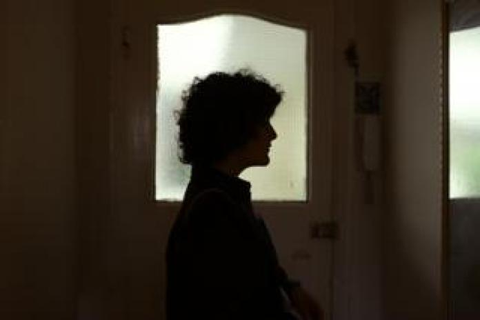 Gilda Bruno looks at herself in a mirror as she leaves her house for an evening