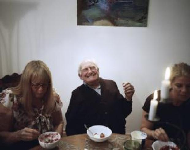 An old man laughs around his family.