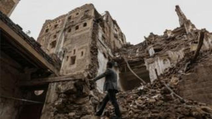 A man walks in the ruins of a damaged building in Sanaa