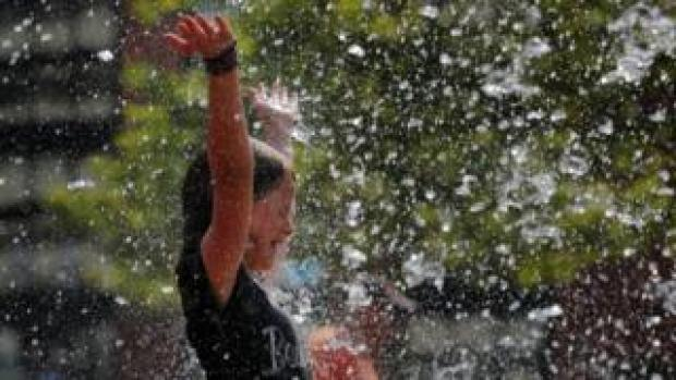 A girl plays in a fountain on the Rose Kennedy Greenway on the first day of a forecasted summer heatwave in Boston, Massachusetts