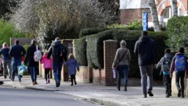 Parents walk their children to school on the last day before their official closure