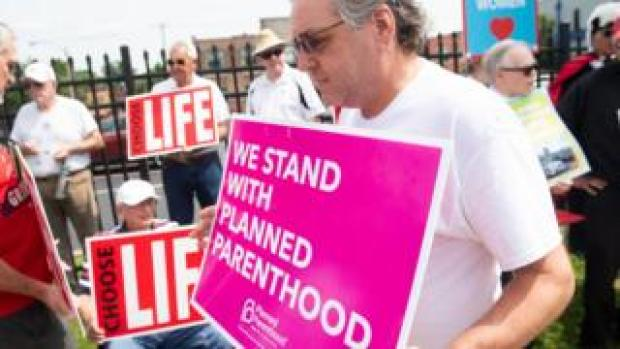 A supporter of Planned Parenthood walks past anti-abortion demonstrators in Missouri in May 2019