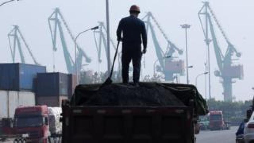 A labourer loads coal in a truck next to containers outside a logistics center near Tianjin Port, in northern China, 16 May, 2019.