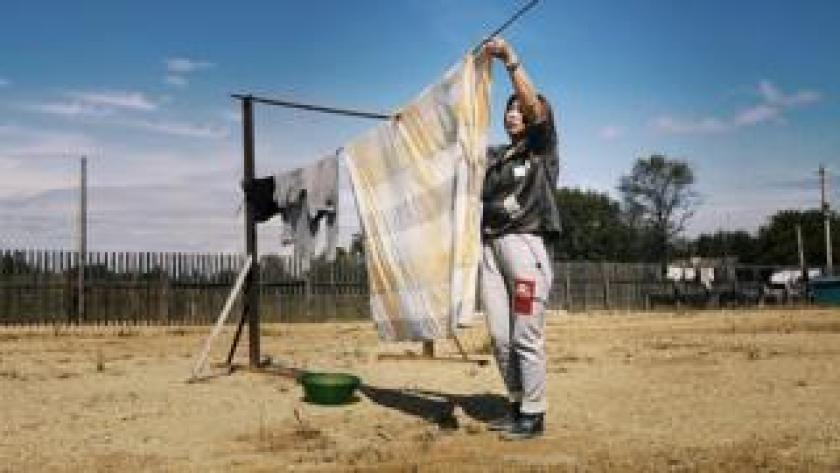 A Chinese woman hangs out the washing on a farm at Dimitrovo