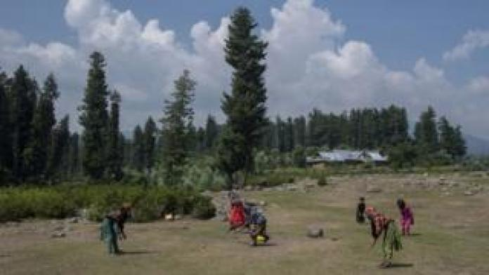 A group of girls play cricket during the break.