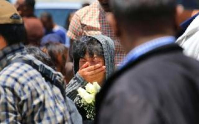 A woman holding flowers cries for a Chinese victim during a memorial service at the crash site of Ethiopian Airlines flight ET302 on March 13, 2019 in Bishoftu, Ethiopia.