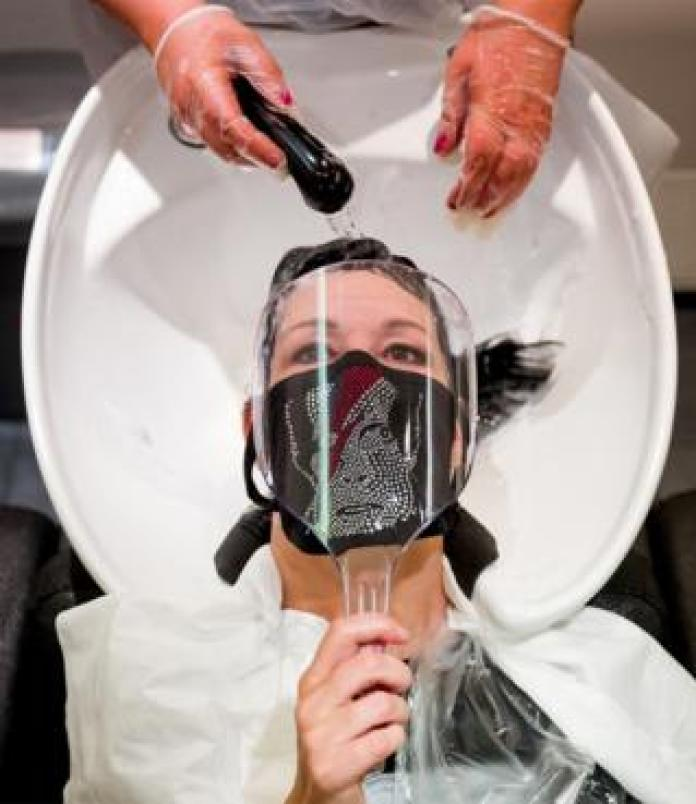 A client wearing a mask with the face of David Bowie has his hair washed in a hair salon