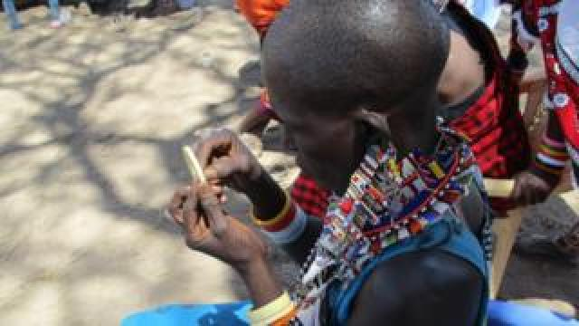 A Maasai woman carries out beading work