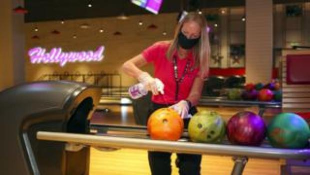 A woman sprays a bowling ball at Hollywood Bowl