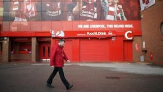 A worker walks by Anfield Stadium, the home Liverpool Football Club