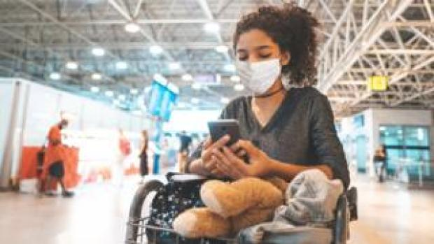 A girl looking at her phone in the airport (stock image)