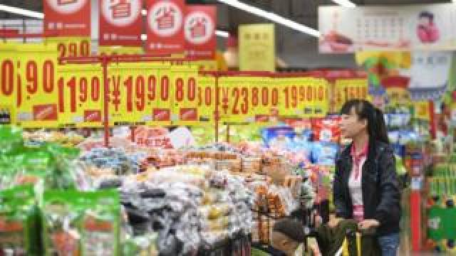 A woman purchases snacks at a supermarket on May 10, 2018 in Taiyuan, Shanxi Province of China