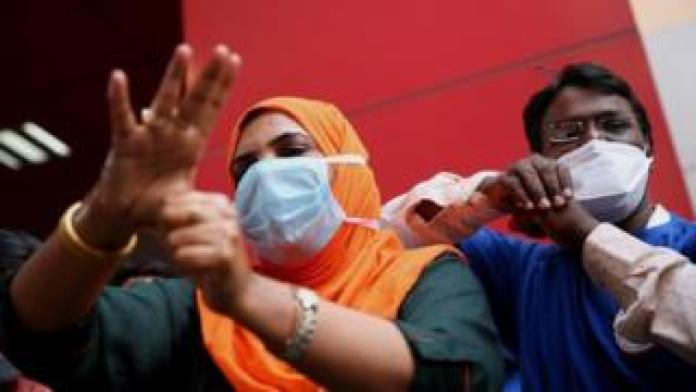 Medical officials in India show to the public how to properly wash their hands using hand sanitisers. File photo