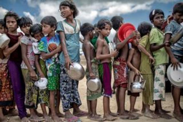 أطفال يحملون مواعين بينما يصطفون للحصول على طعام