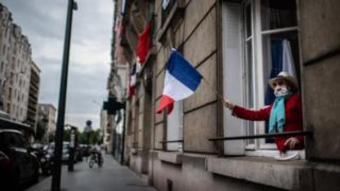 Woman waving the French flag by the window with a coronavirus mask in a Parisian suburb
