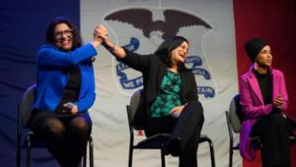 trump Rashida Tlaib high-fives Pramila Jayapal, while sitting next to Ilhan Omar, on stage at the event in Iowa