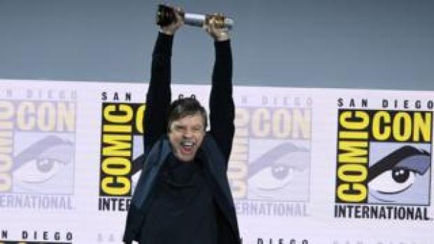 Mark Hamill smiles as he holds up the Icon award at Comic Con