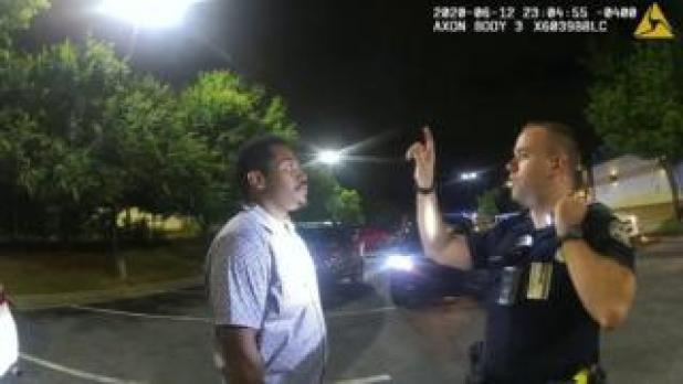 Garrett Rolfe conducts a field sobriety test on Rayshard Brooks in a Wendy's restaurant car park