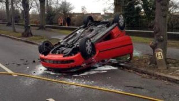 A red Vauxhall Corsa on its roof