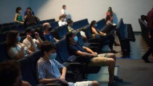 Spectators wear face masks in a cinema